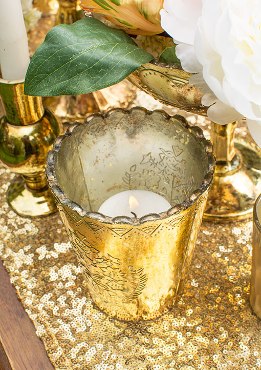 Illuminate the relief pattern on this candle holder by placing a votive candle inside. Style around it with a sequin table runner.