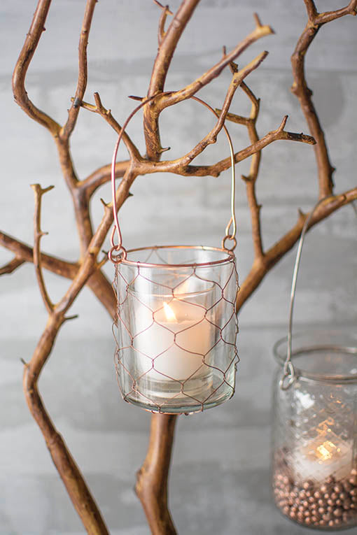 Fill this country chic vessel with a votive candle for romantic illumination on tree branches or shepherd hooks.