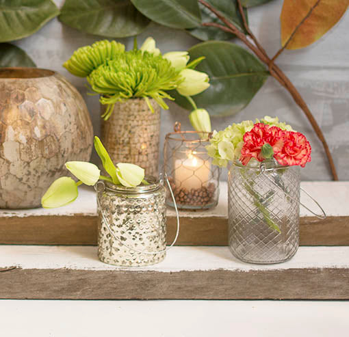 Complement the diamond relief pattern on this clear glass vase with our mercury glass hobnail vessel and copper wire candle holder. Embellish these decorations with our faux flowers that stay forever in bloom.