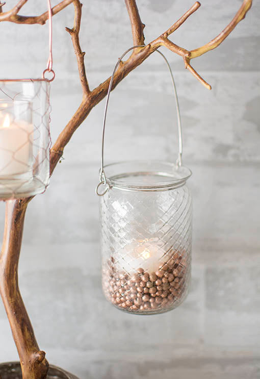 Add vase filler and a votive candle to this holder for romantic illumination in your industrial chic wedding. Arrange this and our other hanging vessels on branches to enchant a natural scene in your event.