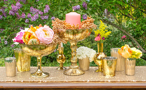 The rich gold tone of our compotes, carved vases and candle holders is an ideal addition to weddings and venue decor. Add bright flowers and metallic berries to complete this display.