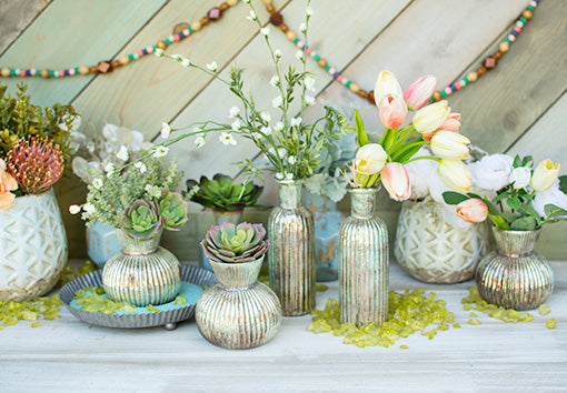 Add our vintage seafoam colored vases to your tablescape for a natural and rich display. Complement these pieces with our flowers, succulents and sprigs, green and blue vase filler, tin pan and a beaded garland in the background.