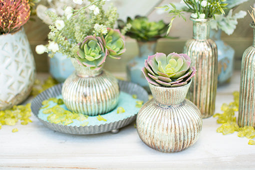 Fill each patina inspired vase with succulents and sprigs and place on top of turquoise colored sand and a tin pan. Accent this garden display with green vase filler.