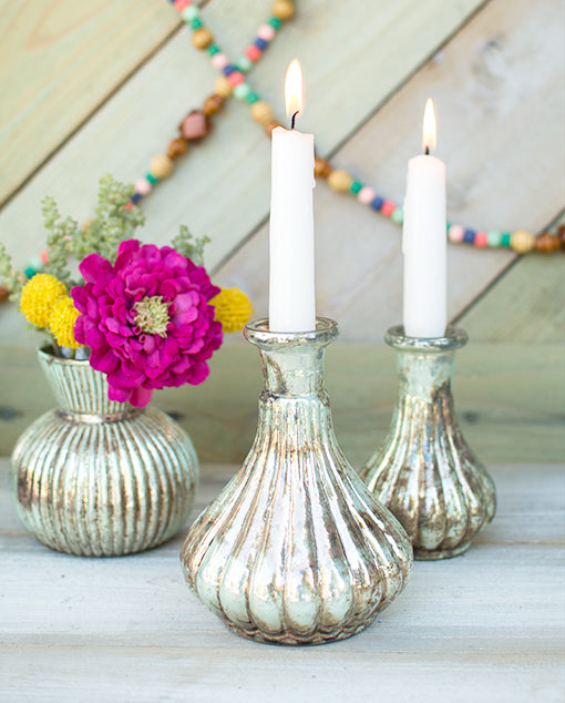 Place a taper candle in each bottle and pair the set with our verdigris inspired vases, a beaded garland and our floral collection.