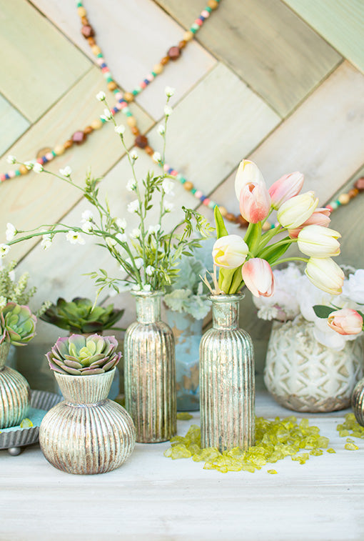 Add tulips and cherry blossom branches to these patina inspired bottles and arrange with our other mercury glass ribbed vases. Accent the garden scene with green vase filler and a beaded garland.