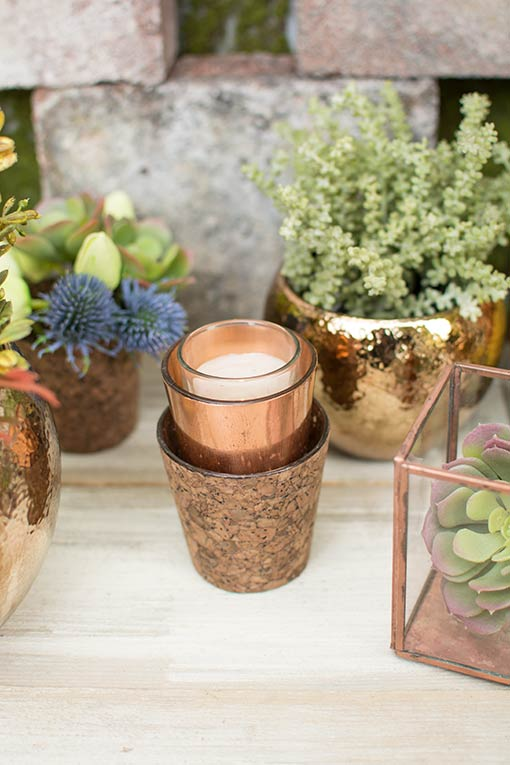 The stark copper colored vase complements the natural cork design of our candle holders. Add a votive candle to create a romantic display with these holders and place the arrangement on a table filled with terrariums, gold toned planter pots and succulents.