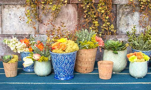 Fill your table with an entire garden! Arrange these cork candle holders and vases with jacquard blue planter pots and seafoam green vases. Add plenty of sprigs, succulents and moss to complete the design.