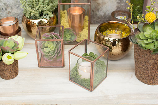 Charm your wedding with a rich garden display. Place a succulent in one terrarium and a candle surround by moss in the other. Finish the tablescape with cork vases, hammered planter pots and floral bouquets.