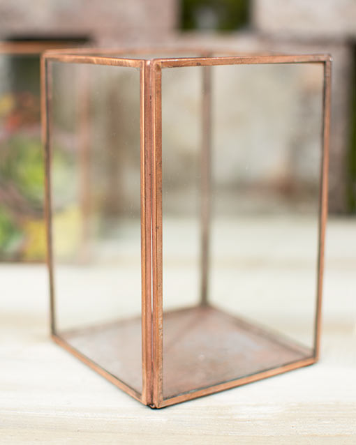Standing 6 inches tall, this 4.25 inch square metal frame includes glass panels and opens at the top.
