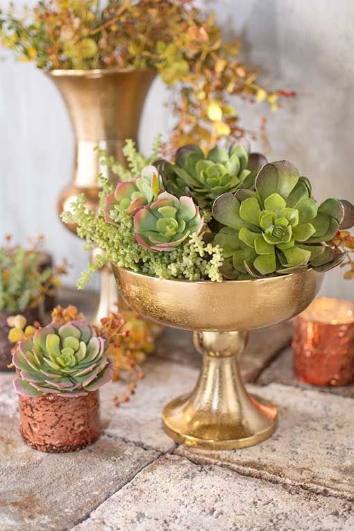 Fill this compote with plenty of sprigs and succulents for a rich display alongside mercury glass accents.