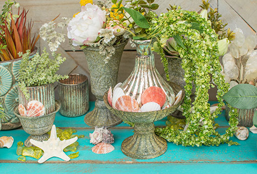 Place a patina inspired vase in this compote with seashells and amaranthus stems for your beach wedding. Add more antique grey vases, seafoam candle holders, seashells and starfish to this display to wow your guests.