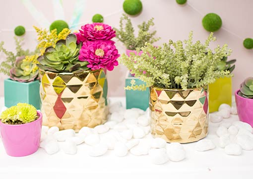 Play with geometric designs in your tablescape with this gold colored planter arranged alongside pink holders, neon green and teal blue square vases, white rock table scatter and realistic succulents.