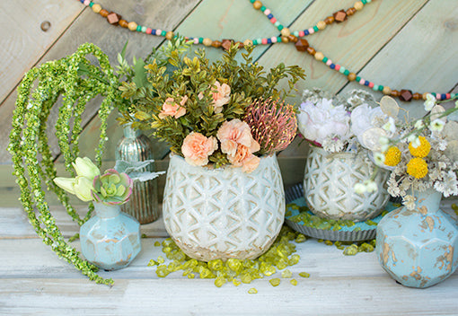 Style your wedding or home tablescapes by placing this planter pot of flowers and sprigs on a bed of green table scatter. Arrange blue geometric vases, bottles, turquoise toned sand and a tin pan with our smaller light blue pot displayed next to this centerpiece.
