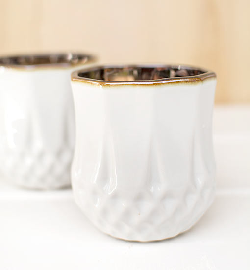 This geometric patterned vessel stands 3.5 inches tall with a 3 inch diameter capable of holding most tea light and votive candles.