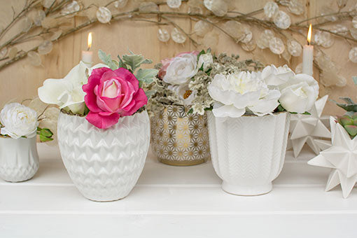 Our herringbone vases capture the modern designs of our gold star patterned holders our white and bronze vases. Complete this tablescape with flowers and sprigs and a silver dollar spray in the background.