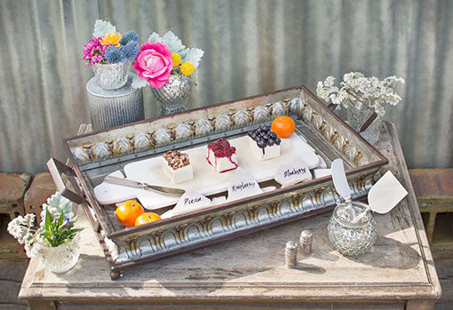 Place a marble cheese board in one of the trays to display sweets and treats on. Embellish this antique style with silver mercury glass candle holders and bud flowers.