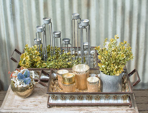 Use two trays to display your favorite accent items such as an articulated candle holder and champagne gold colored candle holders. Fill around these decorations with greenery, vase filler and a corrugated metal vase.