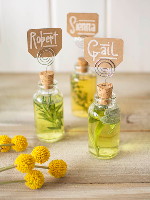 Place a spiral pick in a cork stopper on petite bottles filled with oil or colored water and an herbal sprig. Add decorative billy button flowers and name cards to complete this summer styled look!