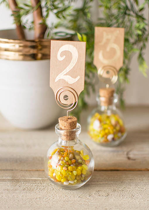 Place these picks in the cork of clear glass bud vases for instant table numbers in your wedding. Fill the clear glass vessel with vase filler to match your color scheme.