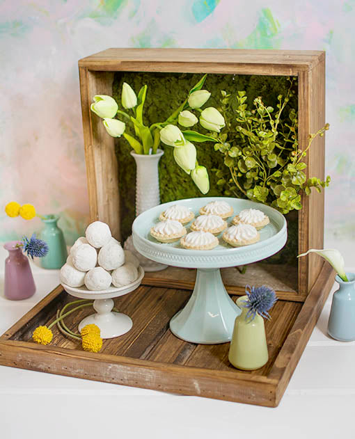 Unfold the interior quality of this wood cake box by creating a colorful dessert display! Add moss mats to the lid and arrange decorative tulips in a hobnail milk glass vase. Place a cupcake and cake stand abundant in treats alongside bud vases filled with vibrant filler flowers.<