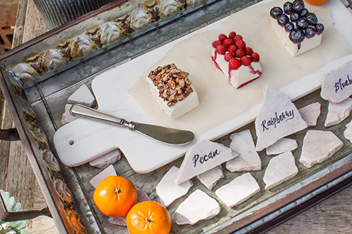 Use these utensils to serve desserts on a marble serving platter in a metal serving tray. Highlight this set with fruits and slate rocks.