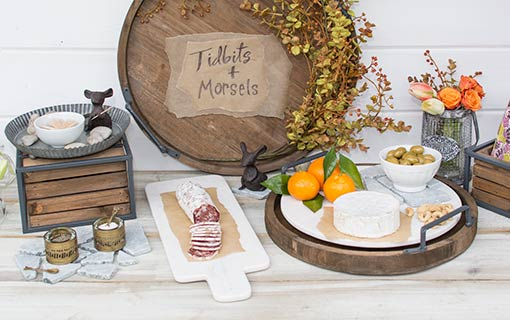 An industrial tasting party is made complete with this marble cheese board. Combine weathered wood trays with faux eucalyptus sprays and cast iron mice for a memorable table setting.