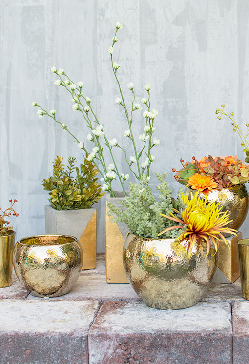 Get more mileage out of your sprigs and sprays by clipping with wire cutters and using as accents throughout your tablescape. Metallic glazed ceramics and gold-kissed concrete set the scene with faux succulents combining with fresh blossoms.