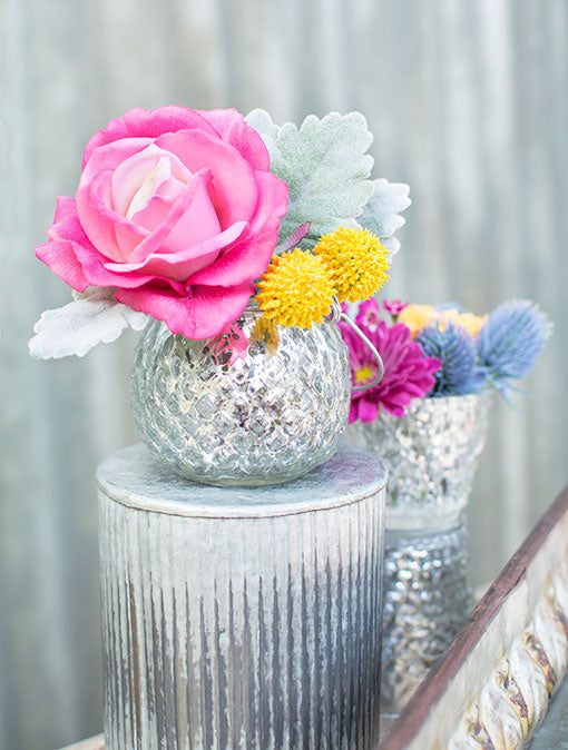 Place this silver mercury glass holder on top of corrugated vases with colorful florals for a unique outdoor wedding design.