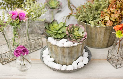 Add white rock vase filler and succulents to this vase as it rests in a tin footed pan. Adorn the table with glass bud vases, sprigs and wire baskets to finish this industrial garden design.