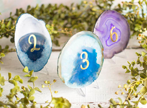 Arrange table numbers for your wedding on these stands with agate slices and metallic number stickers.