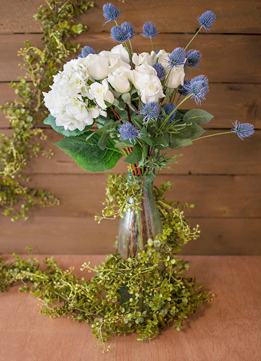 Create the perfect summer bouquet for your wedding by arranging decorative roses, hydrangeas and thistle in a clear glass bubble vase. Wrap the eucalyptus garland around it for a secret garden theme.