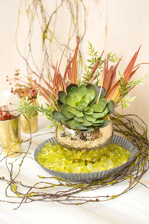 Accent your succulents and greenery with the vibrancy of our rust colored realistic tall grass. The rich colors of this stem complement the gold toned planter pot as it rests in a tin pan. Finish the look with a moss vine and vase filler.