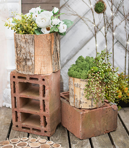 Gather several berry sprigs and nestle into moss-filled reclaimed wood vessels for a woodland ready arrangement.