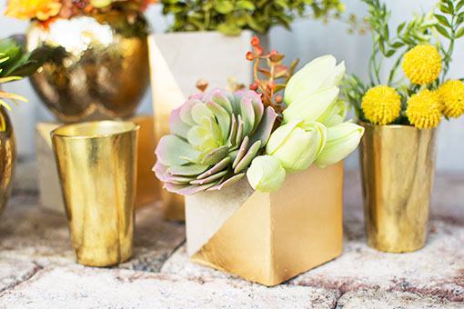 Compose a modern tablescape combining the fresh appearance of tulips with realistic succulents inside gold-dipped concrete vases.