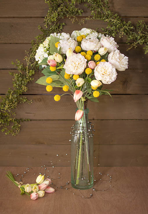 Create a lush bouquet of tulips, peonies and billy buttons in a clear bubble glass vase with silver beaded wire wrapped around the base for an elegant rustic centerpiece.
