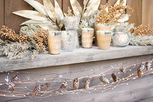 Adorn your wedding tables in this glitter stem, realistic bay leaf branch, our gold toned berry sprig, champagne toned candle holders and geometric bud vases. Finish the scene with a pinecone garland and copper wire fairy lights.