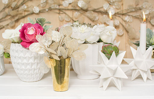 Fill a gold toned bud vase with trimmed silver dollar stems and pair it alongside textured white planter pots for your modern wedding design.