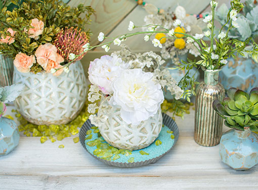 Wild blooms and sumptuous succulents are at home in exotic ceramics nested among bright table scatter.
