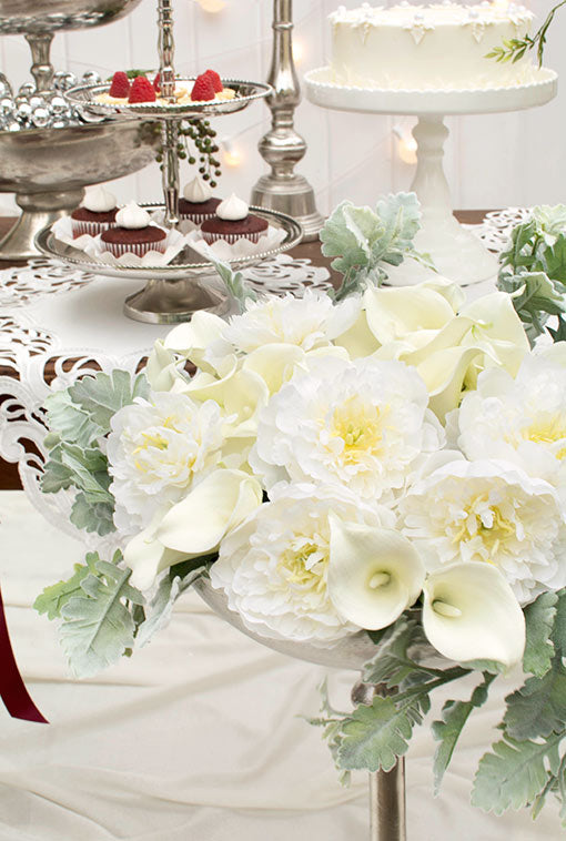 Bright white peonies and elegant calla lilies share a standing compote with lifelike dusty miller for a clean and stately affair.