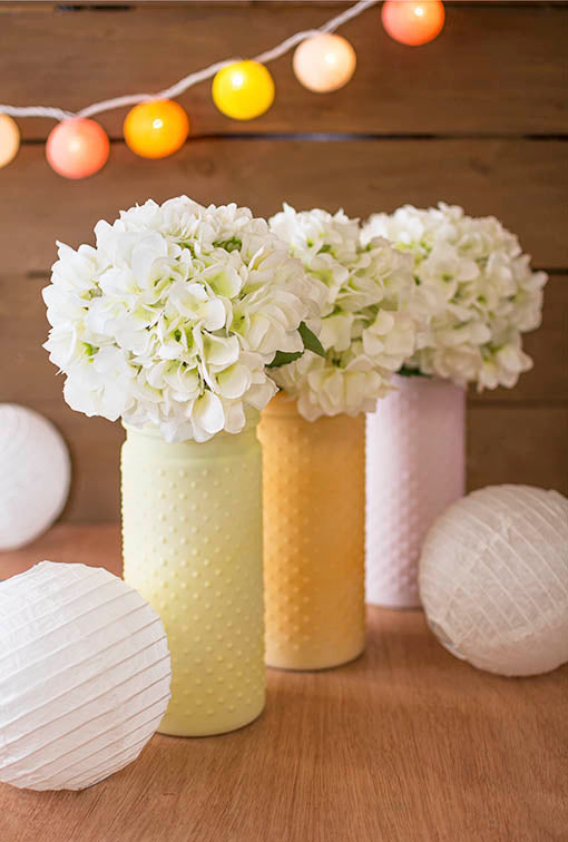 Abound hobnail vases with these decorative white hydrangeas for blooming spring decor! Add paper lanterns to modernize the tablescape.