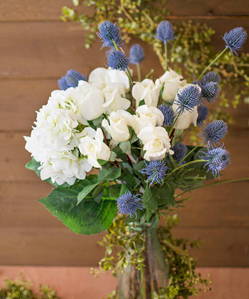 Decorative hydrangeas, thistle and roses complement summer weddings and outdoor events as they thrive in clear bubble glass vases.