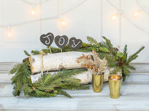 Create a joyful display for your woodland wedding with this swag wrapped around birch logs with chalkboard heart stakes accenting its natural details. Complete the scene with gold toned candle holders, arborvitae stems and berry sprigs.