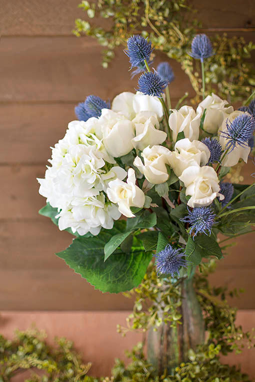 Set a bouquet of decorative roses, hydrangeas and thistle in a clear bubble glass vase as a centerpiece in your summer wedding. Wrap our realistic eucalyptus garland around the set to bring in more garden style.