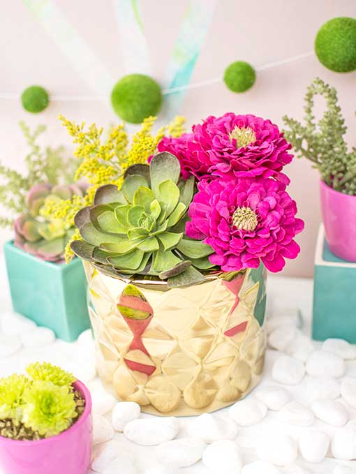 Succulents add a unique quality to events and weddings. Place them alongside bright florals in a geometric planter pot for a vibrant addition to your table.