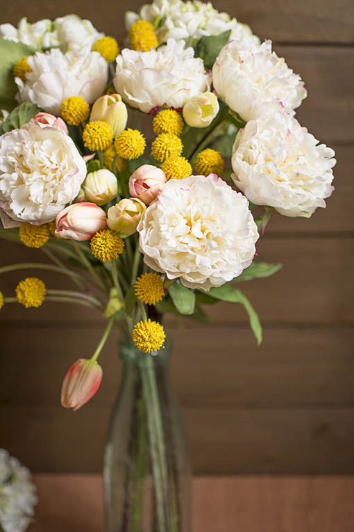 Create a fresh centerpiece in your spring wedding by filling a clear bubble glass vase with our decorative peonies, billy buttons and tulips.