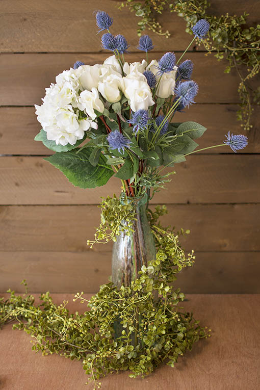 Embellish these thistle stems with decorative roses and hydrangeas in a clear bubble glass vase. Wrap a eucalyptus garland around the bouquet for an enchanting centerpiece.