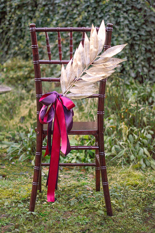 Create unique chair sashes using our gold leaf branches with sleek double faced ribbon in the colors of your event.