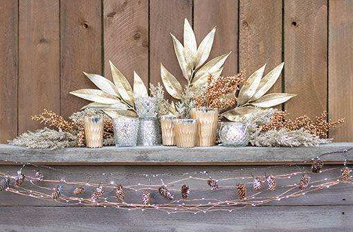 Create a scintillating holiday mantel pairing mercury glass, glittering branches, icy pinecone garland and extra long fairy lights with our stylish gold leaf sprays.