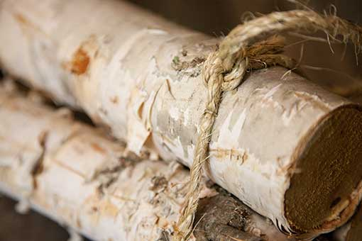 The rope securely attached to the logs to keep this bundle from sliding in your decorating designs.