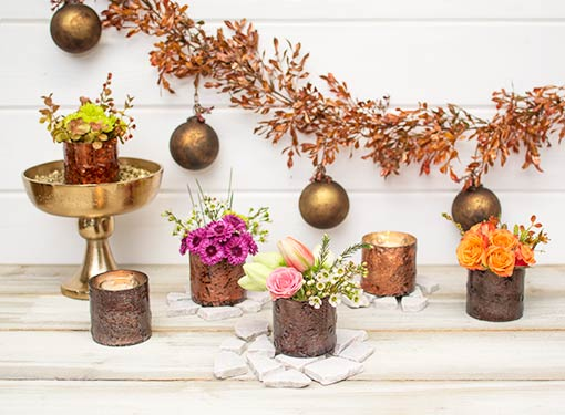Create a luxurious centerpiece at your wedding or event by combining our matte brown candle holders with copper mercury glass vessels, a gold colored compote, realistic swag and marbled ornaments.